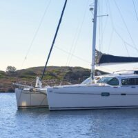 white catamaran anchored next to island in mediterranean