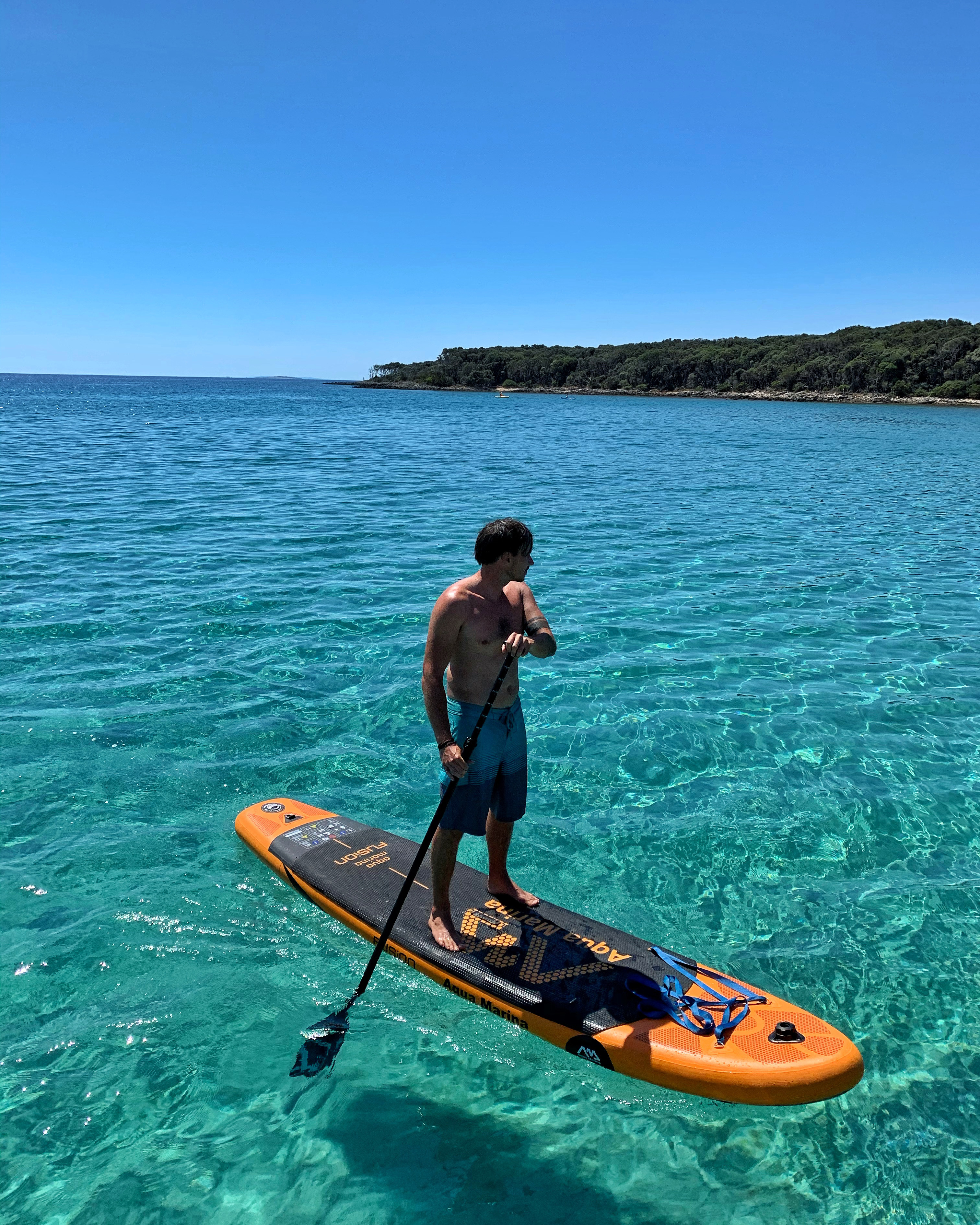 man on orange stand up paddleboard in clear turquoise waters near cres island croatia