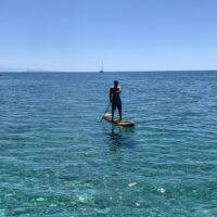 man on an orange stand up paddleboard in turquoise waters off cres island croatia