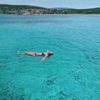 woman floats in turqoise adriatic sea while on croatia sailing adventure