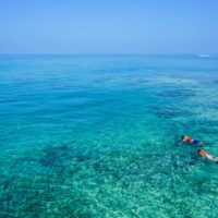 two people snorkeling in clear blue waters