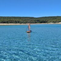 woman on stand up paddleboard in clear blue bay near cres island on croatia sailing adventure
