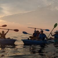 kayakers on calm water at sunset