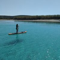 woman paddles a stand up paddleboard to a beach in croatia