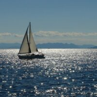 sailboat on the calm Adriatic Sea with mountains in the background