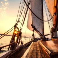 sails and wooden deck of a sailboat against the sky at sunset